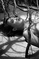 Pretty Filipino nude young woman on beach in tree shadows 