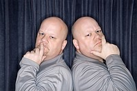 Caucasian bald identical twin men standing back to back and looking at viewer with hands to mouth