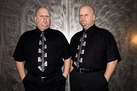 Caucasian bald mid adult identical twin standing together looking at viewer