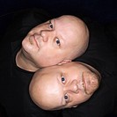 Aeriel view of Caucasian bald identical twin men sitting back to back and looking up at viewer