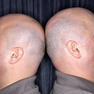 Close up of Caucasian bald identical twin men standing back to back