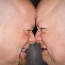 Close up of Caucasian bald mid adult identical twin men standing face to face with angry expression