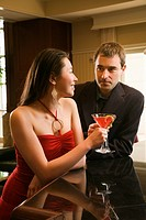 Taiwanese mid adult woman and Caucasian man at bar toasting martinis