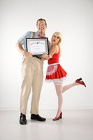 Caucasian young man dressed like nerd holding certificate with Caucasian young blonde woman dressed in french maid outfit