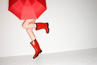 Legs of young Caucasian woman in red boots holding red umbrella and jumping