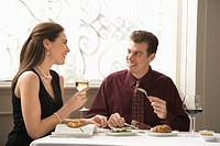 Mid adult Caucasian couple dining in restaurant and smiling