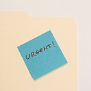 Folder with a sticky note attached reading urgent