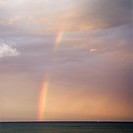 Rainbow spreading across sky on coast