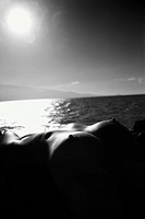Close up of Filipino young nude woman lying on back against ocean and sun in sky