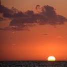 Sun setting over horizon of ocean