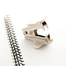 Staple remover on top of an open spiral bound notebook