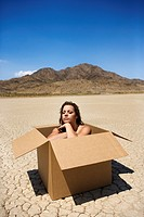 Pretty nude young woman sitting in box in cracked desert landscape in California