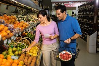 Caucasian mid_adult couple grocery shopping for fruit