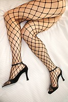 Caucasian woman's legs lying on bed in fishnet stockings and high heel shoes