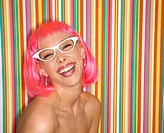 Portrait of attractive Caucasian young adult woman wearing pink wig against striped background making sassy expression looking at viewer