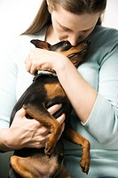Caucasian woman holding and kissing Miniature Pinscher dog