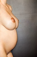 Side view of nude pregnant Caucasian female young adult standing (thumbnail)