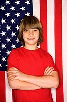 Portait of Caucasian boy with arms crossed with American flag in background