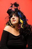 Portrait of Caucasian woman in unique makeup and clothing against red background (thumbnail)