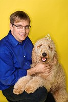 Middle-aged Caucasian man with Goldendoodle dog (thumbnail)