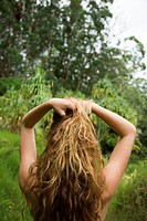 Back view of Caucasian young adult woman in lush forest holding up long wavy hair