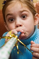 Caucasian girl blowing noisemaker and making facial expression (thumbnail)