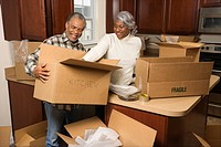 Middle_aged African_American couple packing moving boxes in kitchen