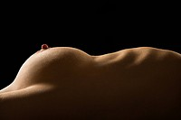 Side view of torso of nude Caucasian woman lying on back