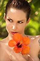 Attractive nude Caucasian tattooed woman holding Hibiscus flower