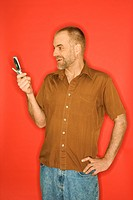 Caucasian man smiling and looking at cellphone standing against orange background