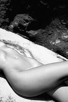Close up of young Caucasian nude womans midsection lying on rock (thumbnail)