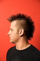 Profile portrait of Caucasian man with spiked mohawk against orange background