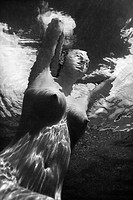 Underwater view of young Asian nude woman partially submerged sitting with hands behind head.