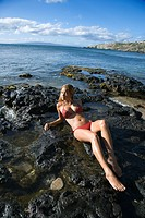 Young adult Asian Filipino female lying on rocky beach
