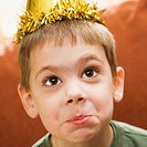 Caucasian boy wearing party hat making facial expression and looking at viewer