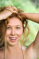 Beautiful happy Caucasian young adult woman holding hair up in lush forest smiling and looking at viewer
