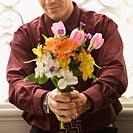 Mid adult Caucasian man holding bouquet of flowers at viewer (thumbnail)