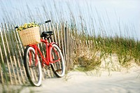 Red vintage bicycle with basket and flowers lleaning against wooden fence at beach