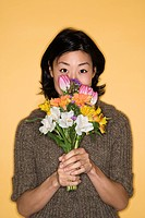 Pretty mid adult Asian woman holding bouquet of flowers up to face
