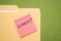 Folder with pink sticky note reading lunch on a green background (thumbnail)