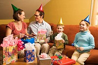 Caucasian family wearing party hats and celebrating a birthday party