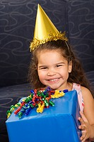 Hispanic girl wearing party hat holding birthday present smiling and looking at viewer