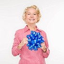 Caucasian senior woman holding blue bow smiling at viewer
