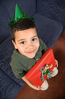 Hispanic boy wearing party hat holding birthday present looking up at viewer and smiling