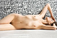 Nude woman lying in front of wall with graphic pattern