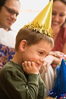 Caucasian boy at birthday party looking to the side and smiling