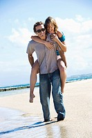 Mid_adult Caucasian man giving woman piggyback ride on beach