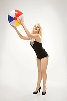 Attractive Caucasian woman wearing swimsuit in pinup pose with beach ball