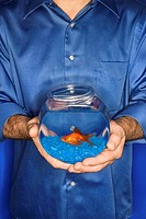 Male Caucasian young adult male holding goldfish in bowl