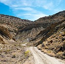 Dirt road winding through rocky desert cliffs of Cottonwood Canyon, Utah